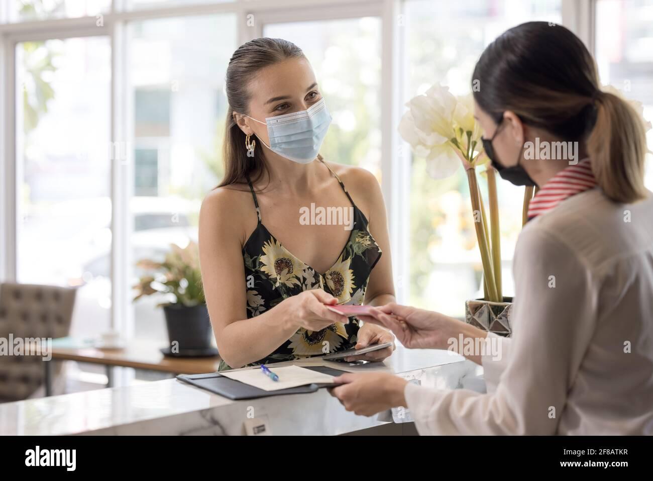 La recepcionista entrega un pasaporte a un turista en te recepción y recepción de un albergue Foto de stock