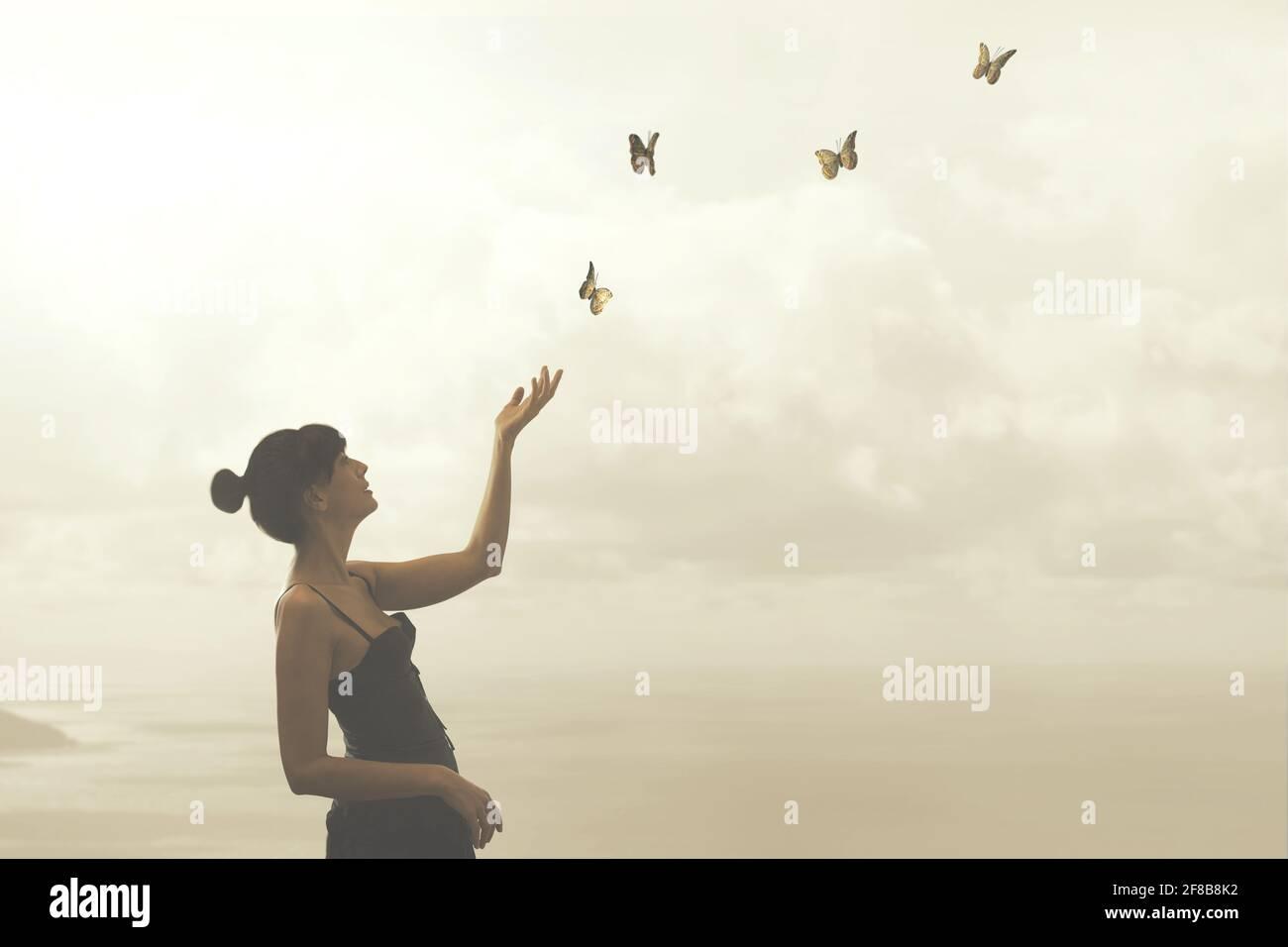 la mujer toca suavemente las mariposas que vuelan libremente Foto de stock