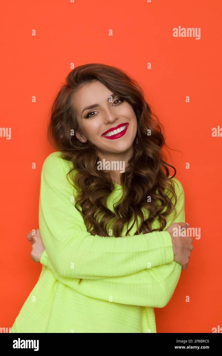 Mujer joven sonriente en un suéter verde lima está posando con los brazos cruzados. Vista frontal. Estudio con cintura para arriba sobre fondo naranja. Foto de stock