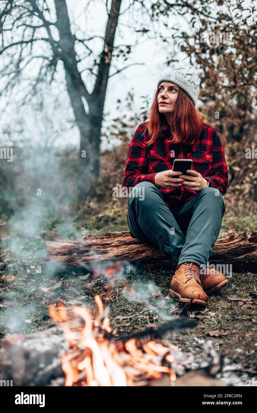 Una chica de viaje con ropa hipster se sienta en un tronco disfrutando, relajándose en el bosque cerca del fuego en camping. Mujer que utiliza el smartphone en la naturaleza Foto de stock