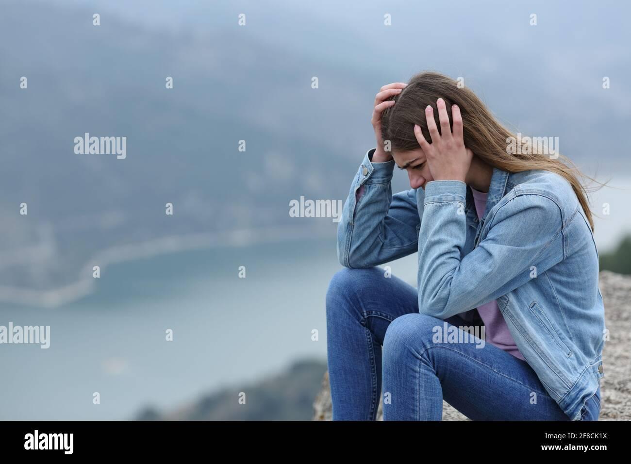 Triste adolescente quejándose sentado solo en un acantilado en el montaña Foto de stock