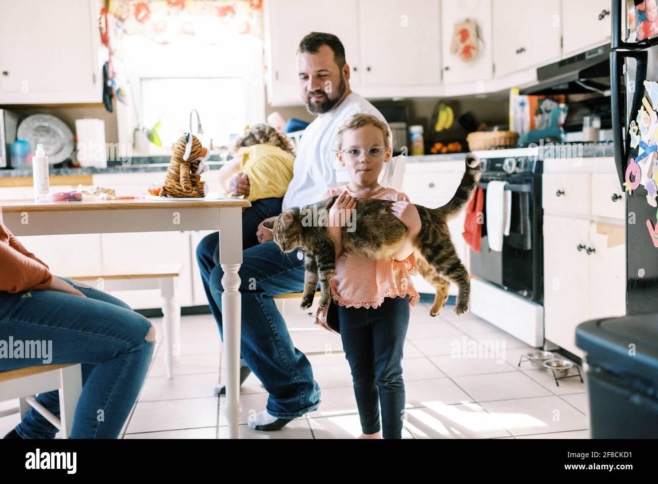 Pequeña niña sosteniendo su lindo gato mascota en ella brazos en la cocina Foto de stock