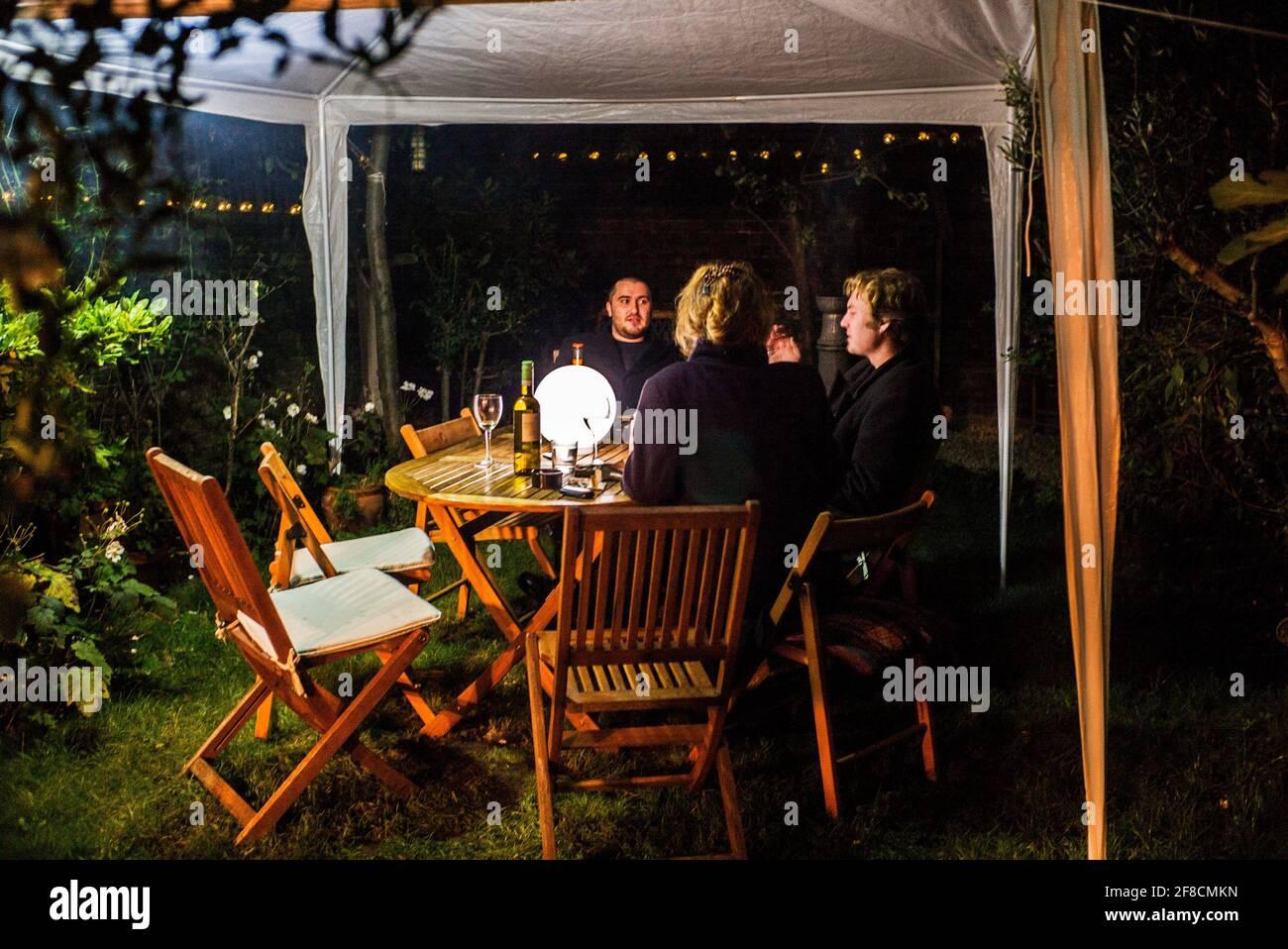 bebidas nocturnas socialmente distanciadas bajo el cenador en el jardín durante restricciones de covid-19 Foto de stock