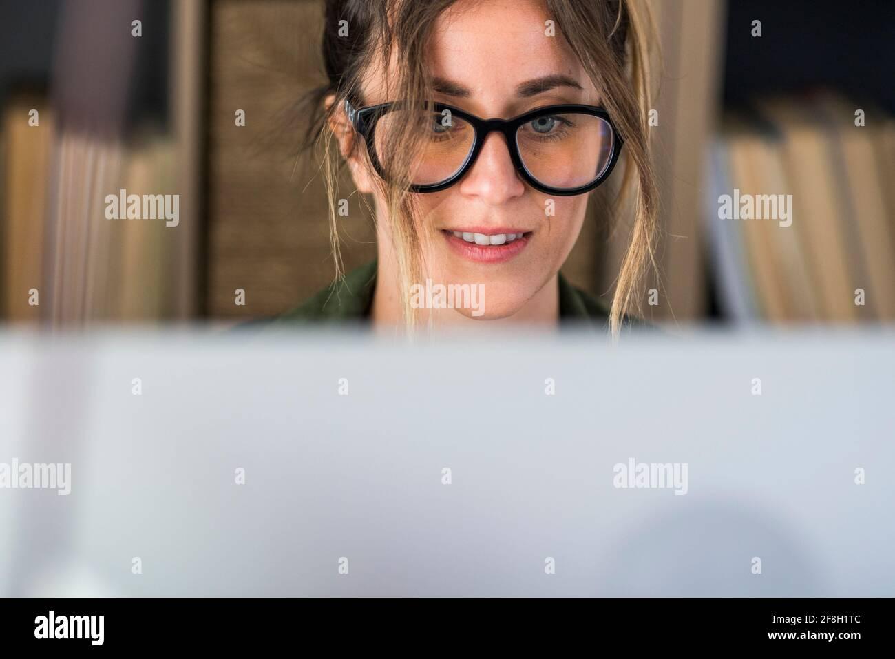 Head shot agradable mujer joven feliz trabajando en la computadora en casa. Atractiva mujer de negocios estudiando en línea, utilizando el software de la computadora portátil, navegar por la web Foto de stock