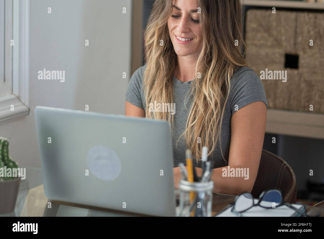 Mujer adulta tipo en el ordenador portátil y sonrisa feliz por trabajo inteligente libre de la actividad de oficina en casa - la gente moderna en línea estilo de vida de trabajo remoto - fem Foto de stock