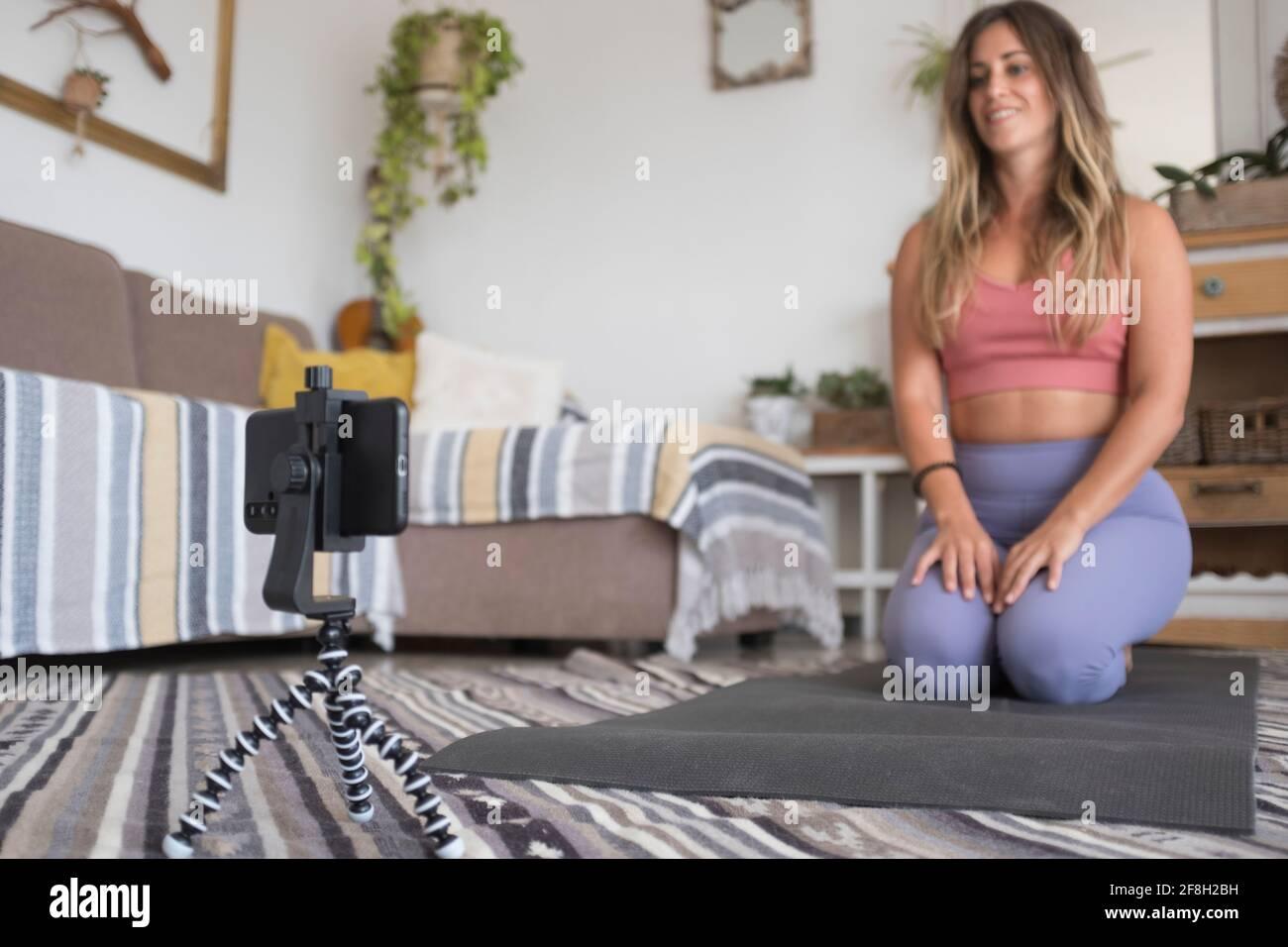Joven entrenador personal trabajo en casa hacer clase en línea utilizando móvil teléfono y conexión a internet: creador activo de contenido de estilo de vida saludable influencer - mo Foto de stock