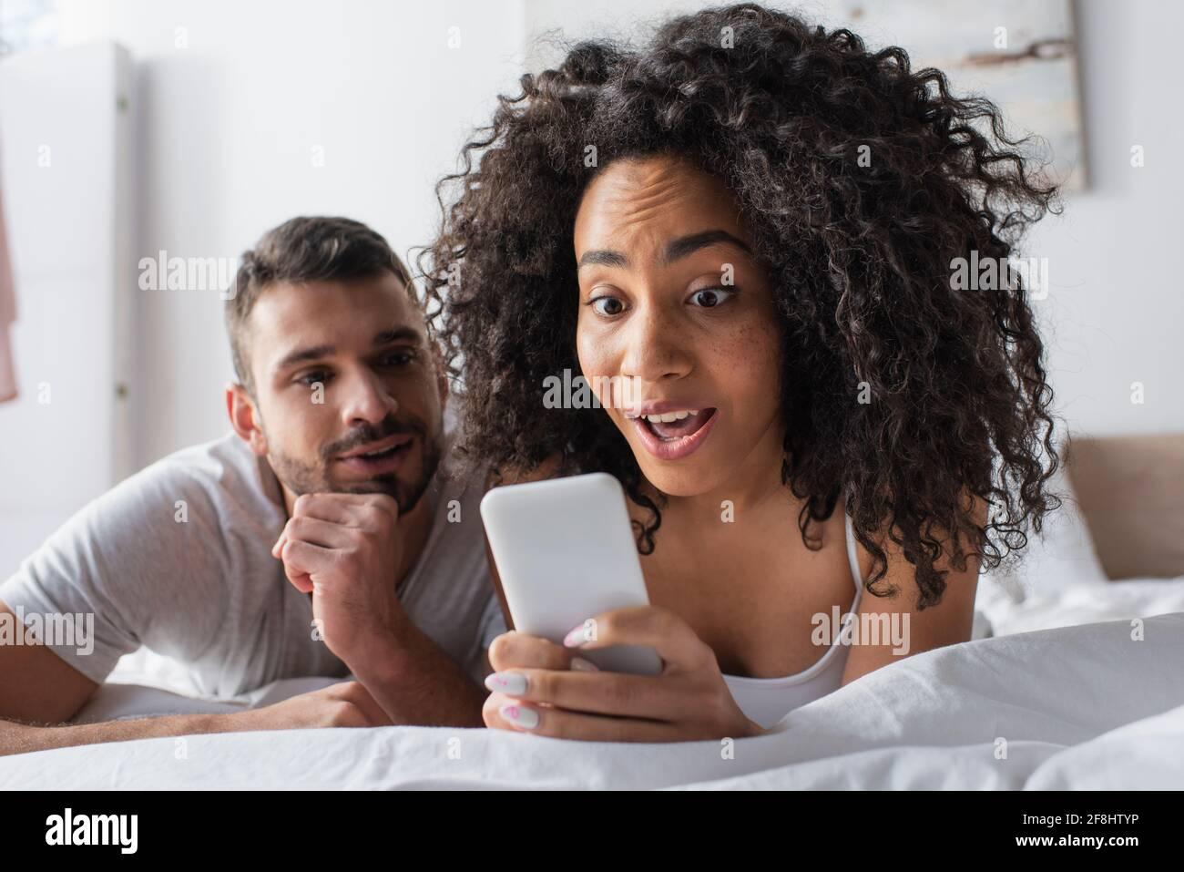 mujer afroamericana sorprendida sosteniendo un smartphone cerca de un novio barbudo fondo borroso Foto de stock