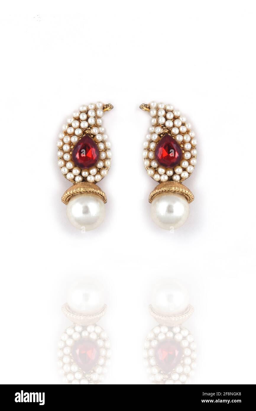 Hermoso par de pendientes perla con piedra preciosa roja sobre un fondo blanco joyería tradicional India, , pendientes de oro nupcial joyas de boda Foto de stock