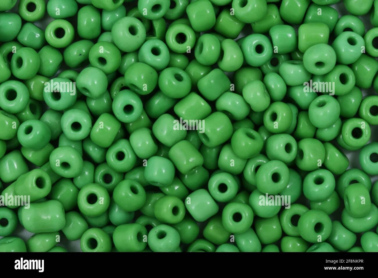 Cuentas verdes sobre el fondo blanco primer plano, macro, hacer collar de abalorios Foto de stock