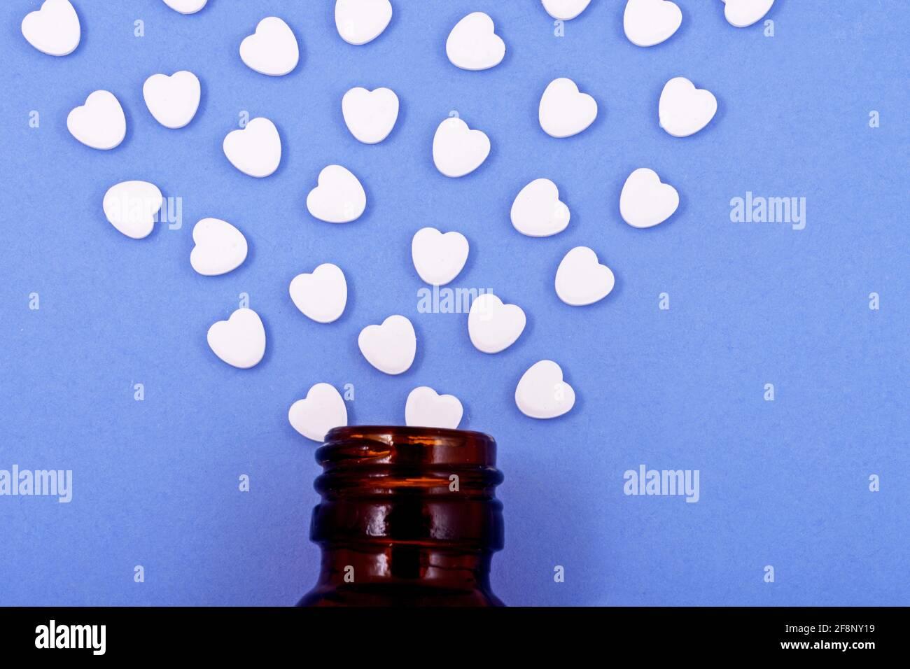 Pastillas con forma de corazón de vidrio de botella sobre un fondo azul Medicamentos que ayudan a las personas Foto de stock