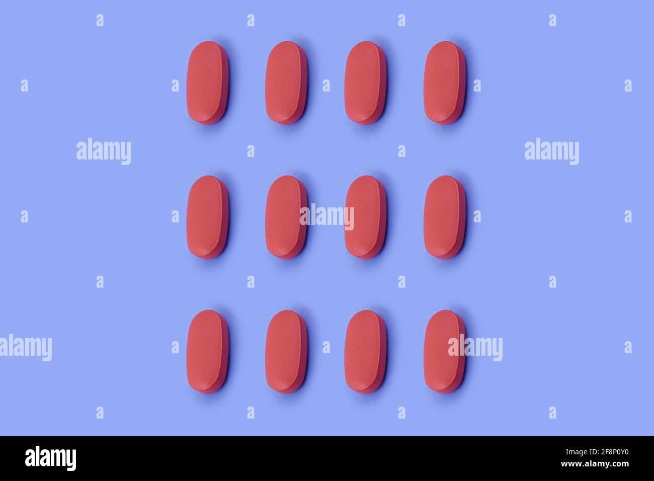 Forma ovalada tableta de medicina farmacéutica sobre fondo azul, Medicina conceptos creativos estilo mínimo con fondo de papel colorido Foto de stock