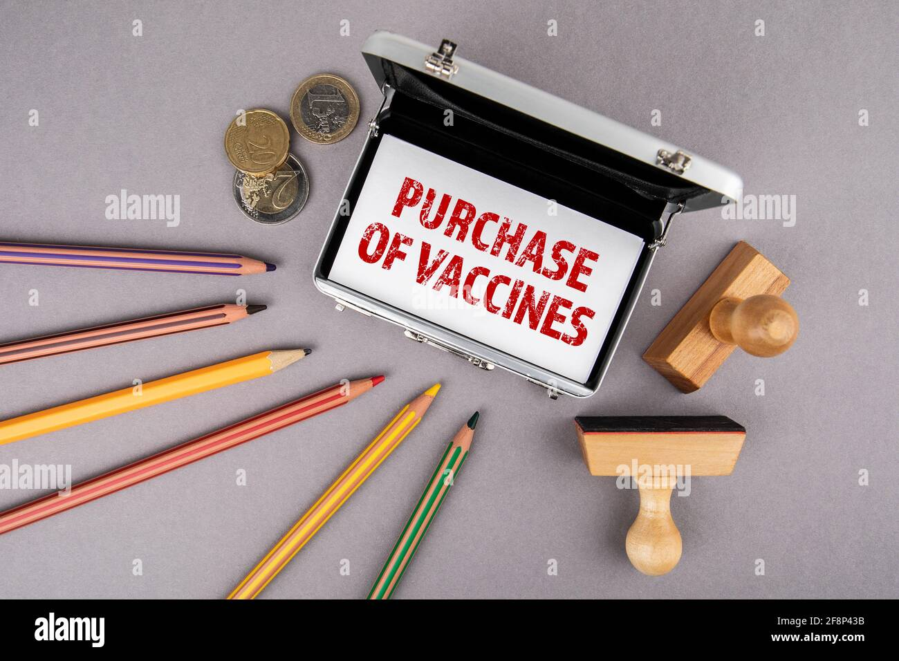 Compra de vacunas. Tarjetas de visita, lápices de colores y dinero en euros en un escritorio de oficina gris. Foto de stock