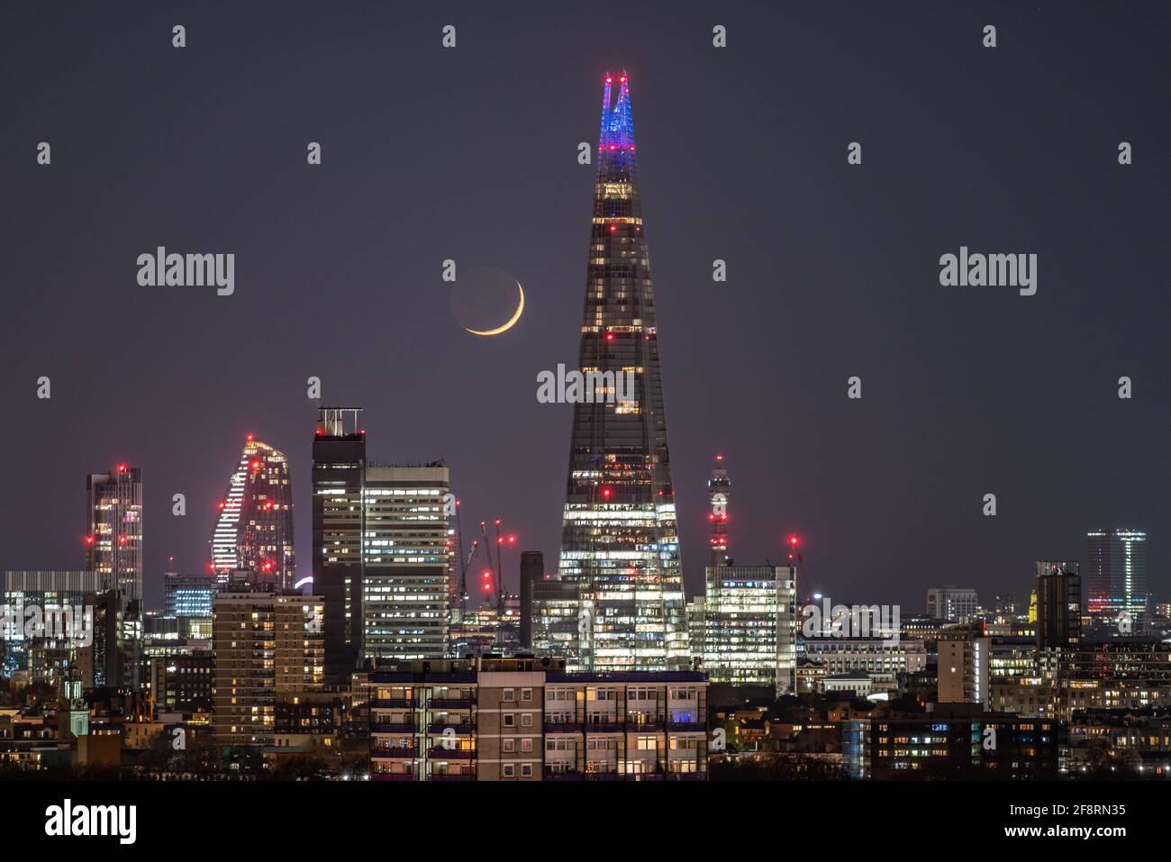 Londres, Reino Unido. 14th de abril de 2021. Clima en el Reino Unido: Una luna Waxing Crescent se pone en las últimas horas del miércoles pasando por el edificio del rascacielos Shard siguiendo una dirección noroeste. Crédito: Guy Corbishley/Alamy Live News Foto de stock