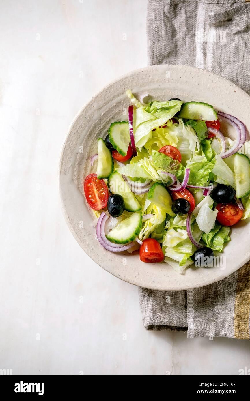 Ensalada de verduras clásicas con tomates, pepino, cebolla, hojas de ensalada y aceitunas negras en plato de cerámica blanca sobre servilleta de tela. Fondo de mármol blanco. Foto de stock