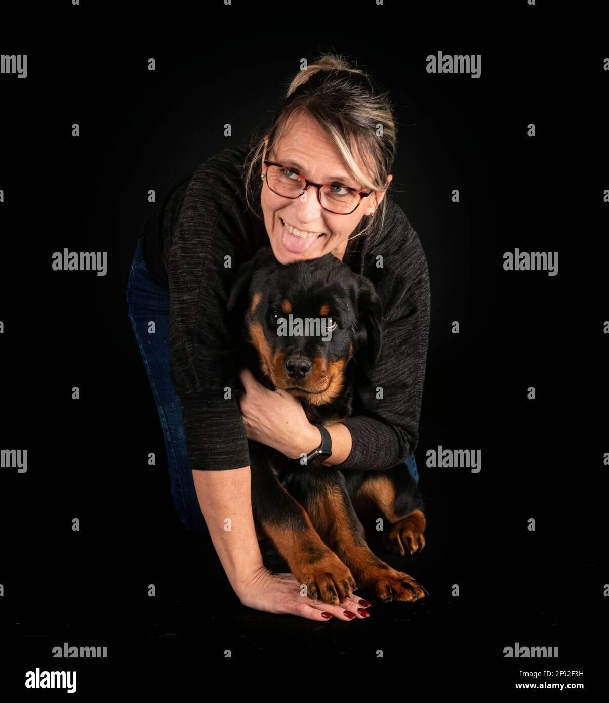 purebred rottweiler y mujer delante de fondo negro Foto de stock