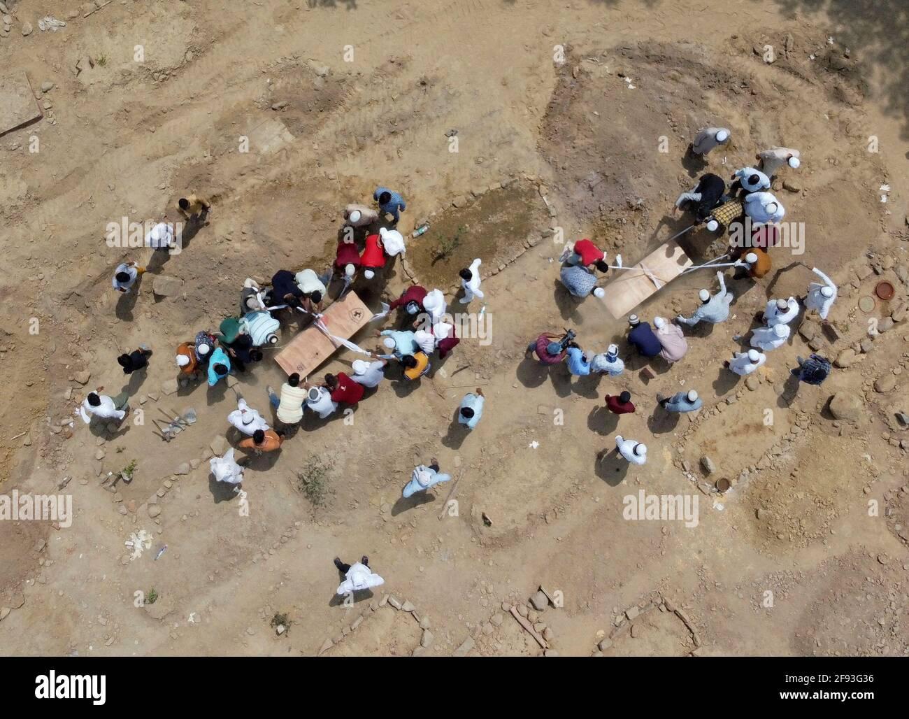 La gente entierra los cuerpos de las víctimas que murieron debido a la enfermedad del coronavirus (COVID-19), en un cementerio en Nueva Delhi, India, el 16 de abril de 2021. Foto tomada con un drone. REUTERS/Siddiqui danés Foto de stock