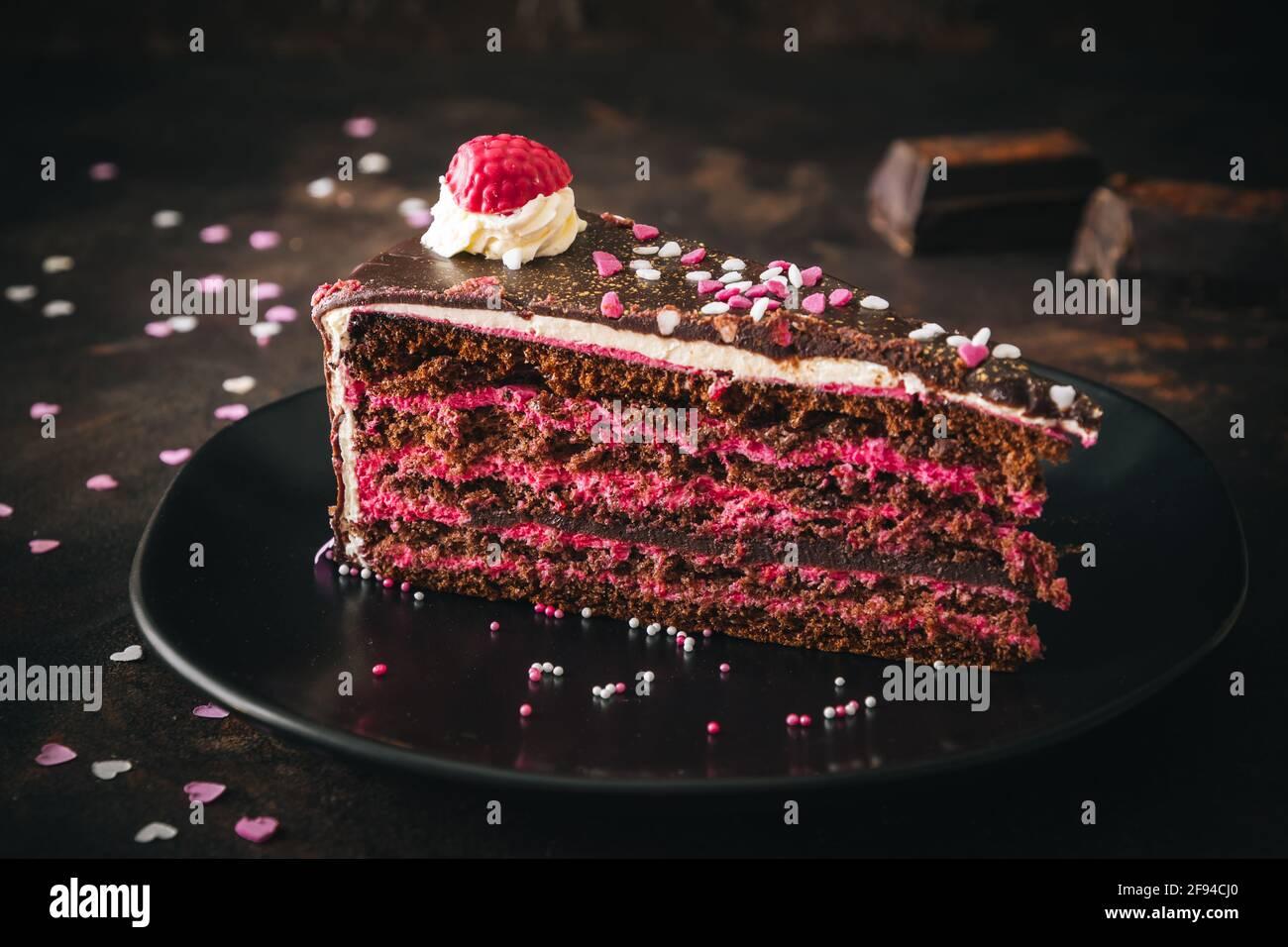 Pieza de torta de chocolate de frambuesa sobre un plato negro fondo marrón oscuro Foto de stock