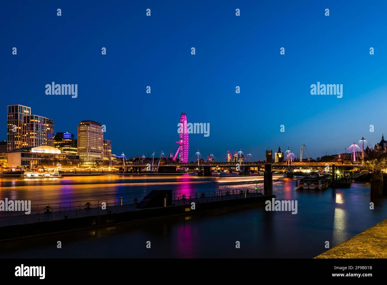 Luces y senderos para barcos en los puentes Hungerford y Golden Jubilee al atardecer, Londres, Reino Unido Foto de stock