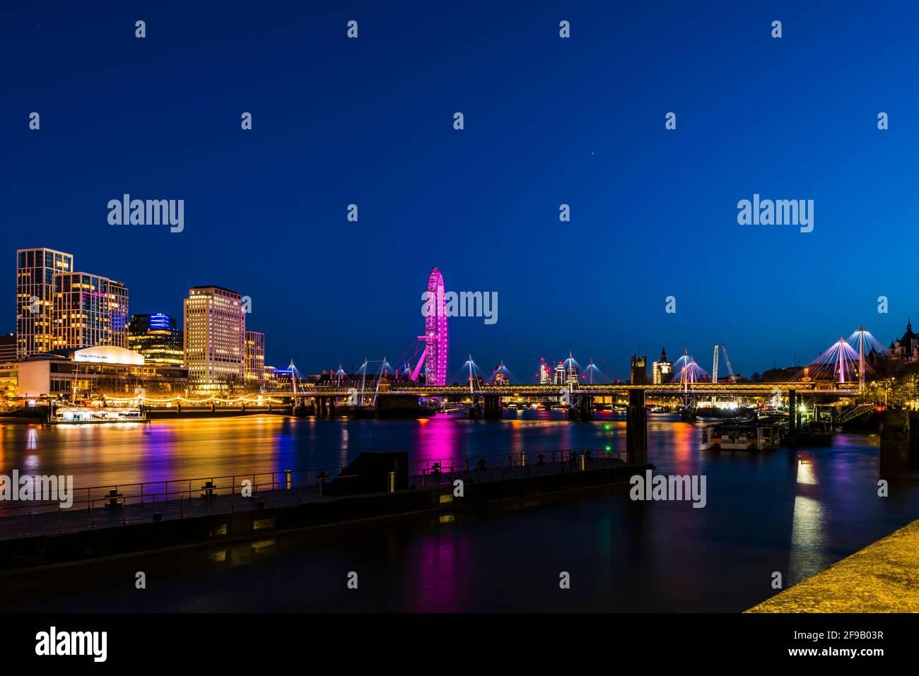 Luces en los puentes Hungerford y Golden Jubilee después del anochecer, Londres, Reino Unido Foto de stock
