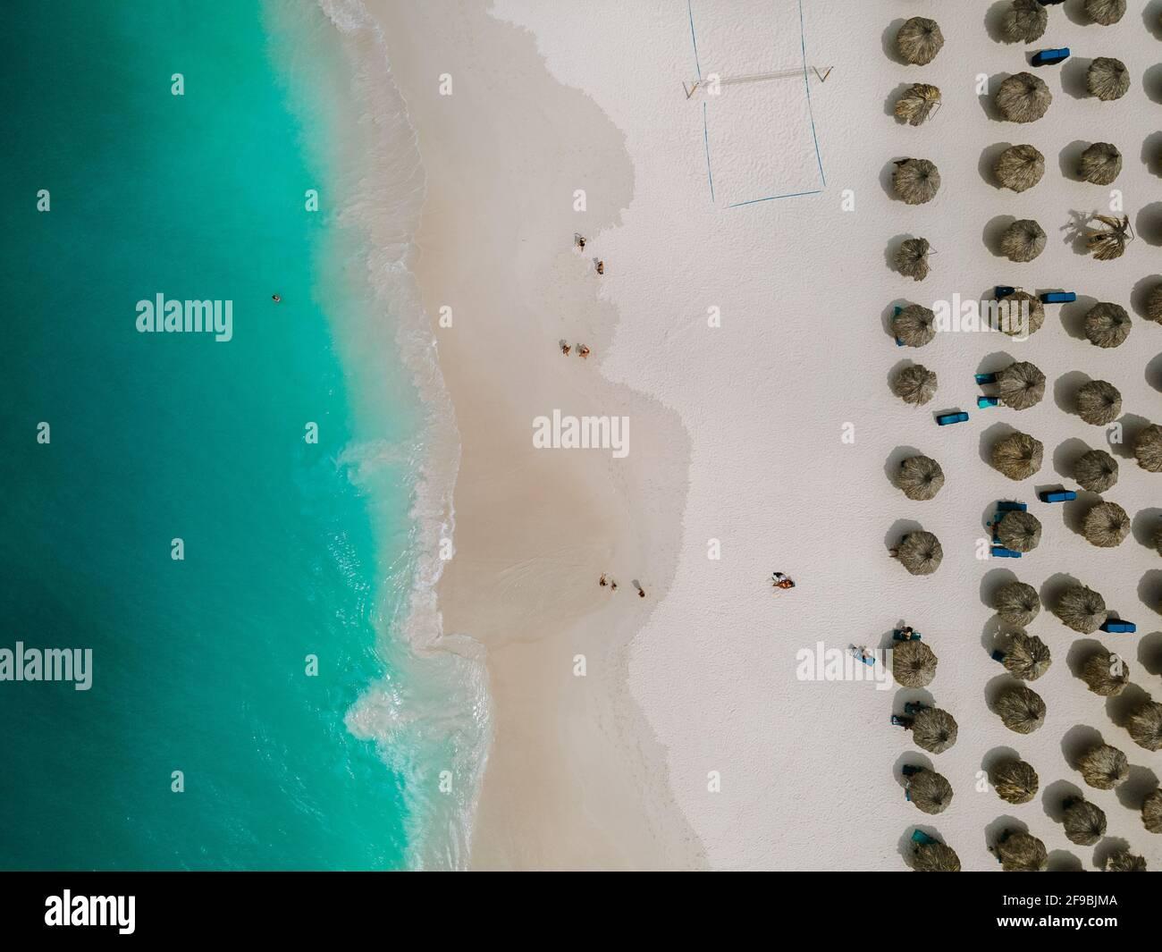 Aérea desde la playa Eagle en Aruba en el Caribe, vista de pájaro en la playa con sombrilla en la playa Eagle de Aruba con océano azul Foto de stock
