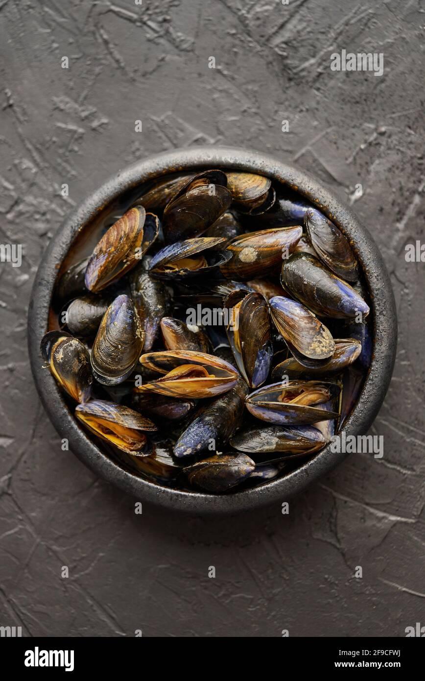 Mejillones de mar frescos y crudos en un tazón de cerámica negro sobre fondo de piedra oscura Foto de stock