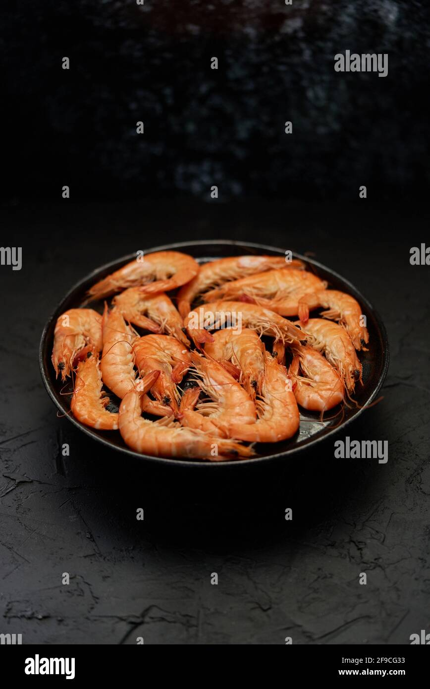 Langostinos de mar grandes hervidos o camarones colocados sobre cerámica negra placa Foto de stock