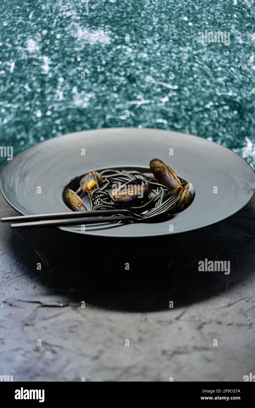 Pasta de espagueti negra de marisco con almejas servidas en plato negro sobre piedra oscura Foto de stock
