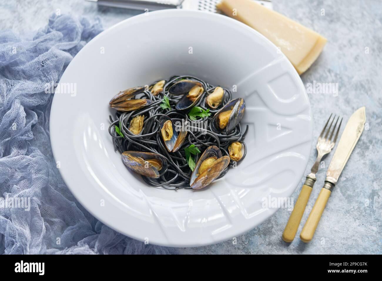 Pasta de espagueti de marisco negro con mejillones sobre fondo de piedra. Comida mediterránea deliciosa Foto de stock