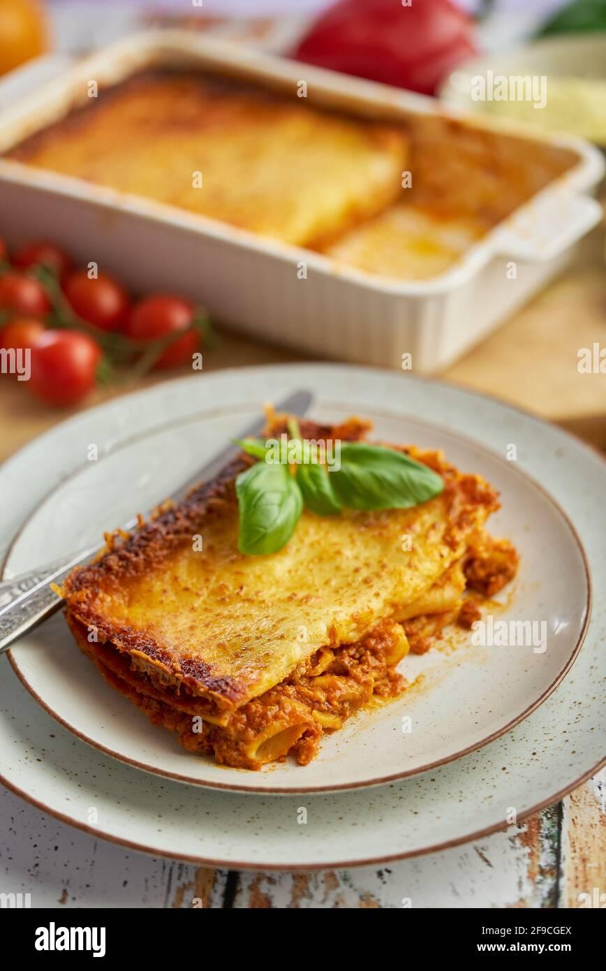 Sabrosas lasaña de carne casera con albahaca fresca y queso parmesano en un plato sobre fondo de madera Foto de stock