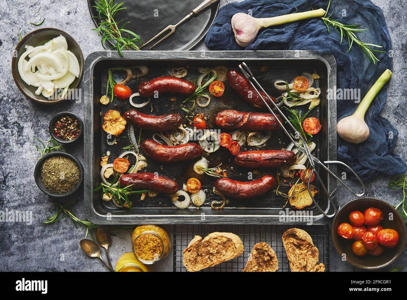 Vista superior de las deliciosas salchichas a la parrilla servidas con cebolla, tomates, ajo, pan y hierbas Foto de stock