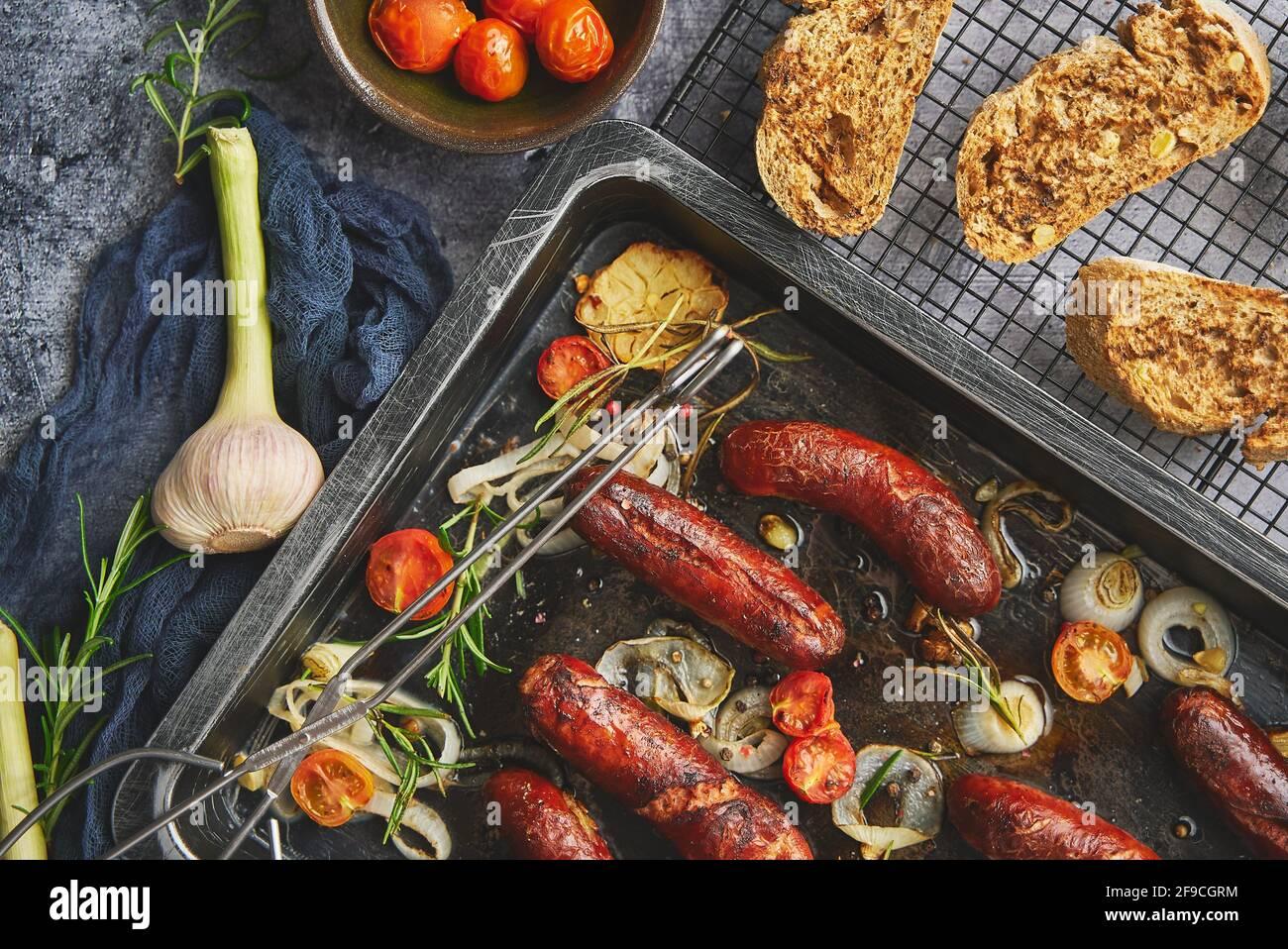 Sabrosas salchichas caseras de romero a la parrilla colocadas en una bandeja de freír de hierro sobre mesa rústica de piedra oscura Foto de stock