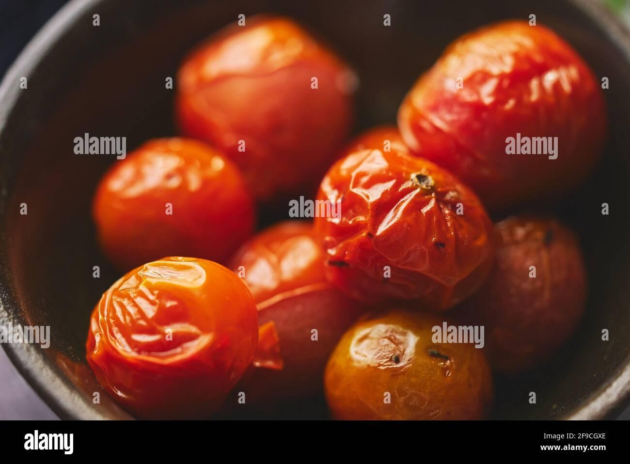 Tomates cherry asados colocados en un cuenco cerámico oscuro. Primer plano de la macro. Foto de stock