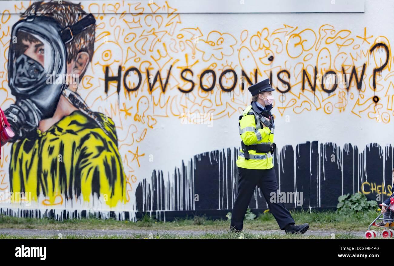 Un Garda pasa por un nuevo mural en el Grand Canal Docks de Dublín por el artista CHELS (Chelsea Jacobs), reflejando el incierto futuro de los niños debido a las restricciones de Covid-19. Fecha de la foto: Domingo 18 de abril de 2021. Foto de stock