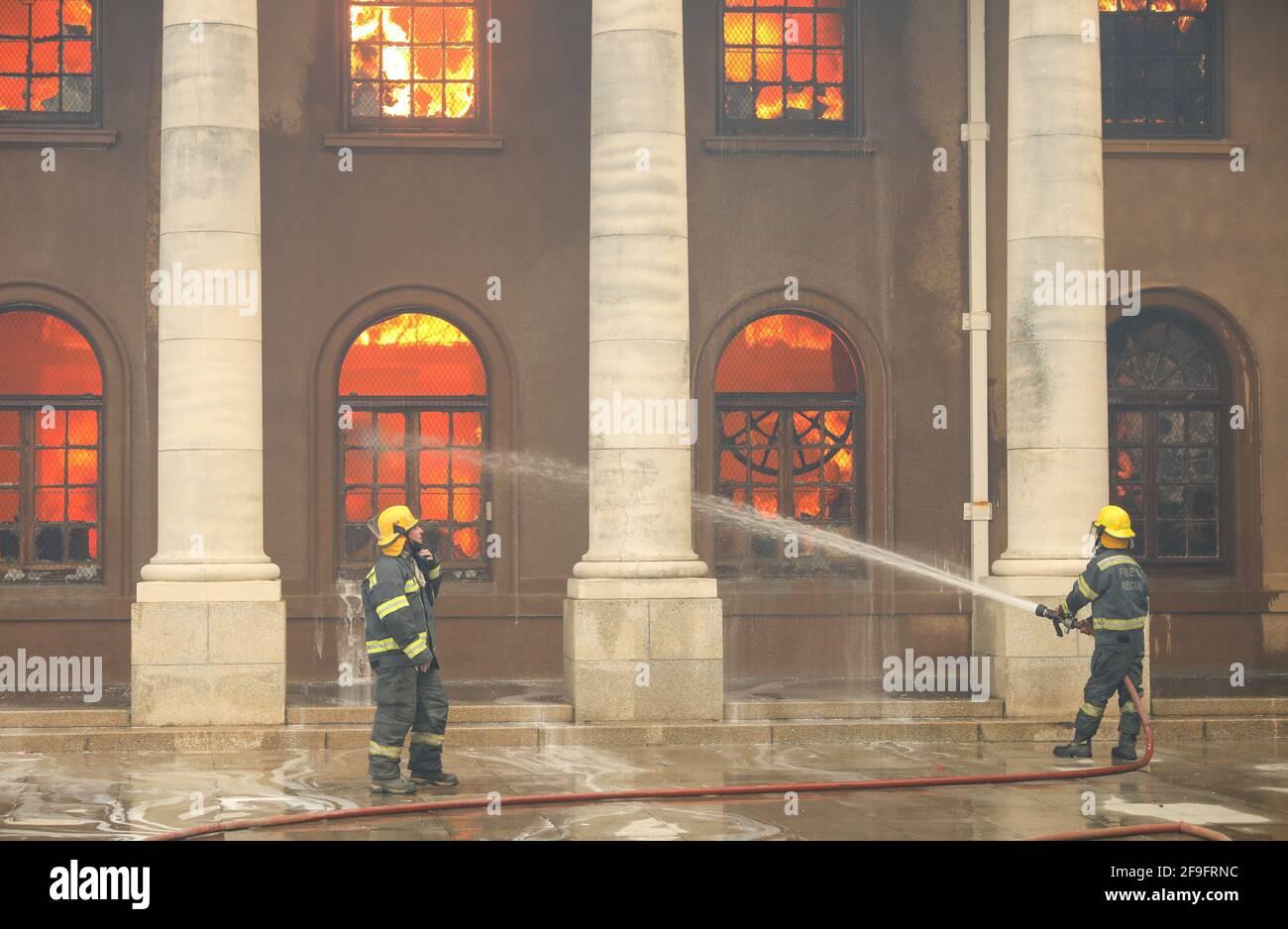 Los bomberos se incendian mientras la biblioteca de la Universidad de Ciudad del Cabo se quema después de que estallara un incendio en las laderas de Table Mountain en Ciudad del Cabo, Sudáfrica, el 18 de abril de 2021. REUTERS/Mike Hutchings Foto de stock