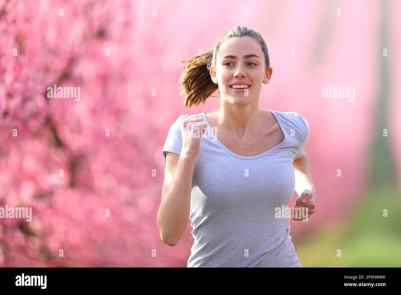 Vista frontal retrato de una mujer feliz corriendo en un campo de flujo hacia la cámara Foto de stock
