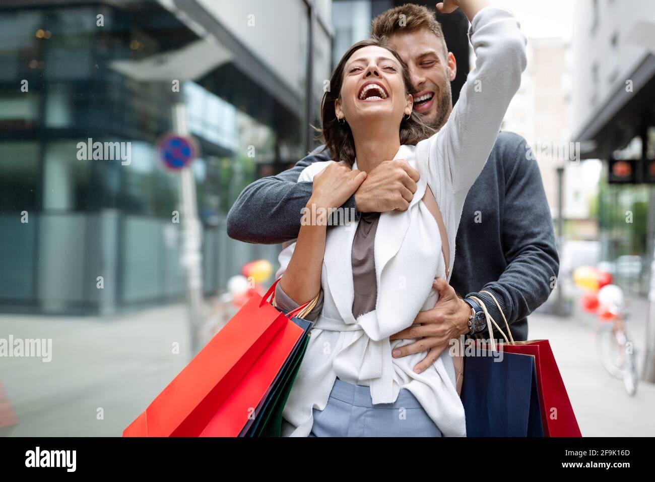 Hermosa pareja joven y cariñosa caminando por la calle con bolsas de compras Foto de stock