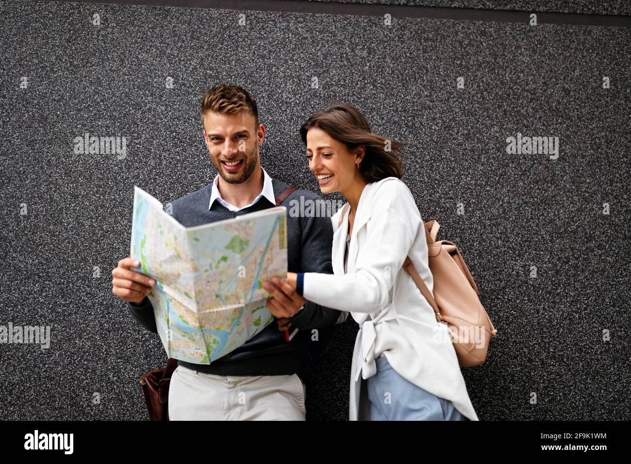 Feliz mujer sonriente y hombre enamorado caminando con mapa en la ciudad Foto de stock