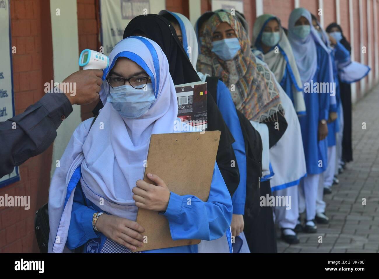 Lahore, Pakistán. 19th de Abr de 2021. Un guardia de seguridad está revisando la temperatura corporal y desinfectando los zapatos de las niñas estudiantes antes de entrar en los Institutos educativos. Gobierno Kinaird niñas escuela secundaria de 9th a 12th grados está reabierto después de largas vacaciones debido a la tercera fase de Covid-19 en Lahore. (Foto de Rana Sajid Hussain/Pacific Press) Crédito: Pacific Press Media Production Corp./Alamy Live News Foto de stock