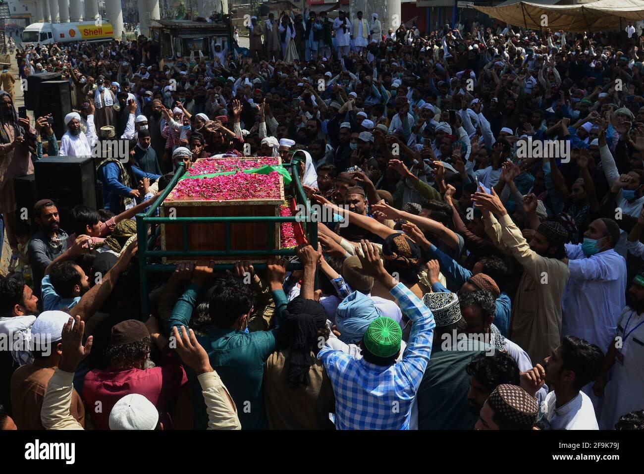 Lahore, Pakistán. 19th de Abr de 2021. Los partidarios del partido de Tehreek-e-Labbaik Pakistán (TLP) llevan el ataúd y gritan eslóganes durante la oración fúnebre de su colega de un camarada que fue asesinado en el enfrentamiento del domingo con las fuerzas de seguridad, Una protesta después de que su líder fuera detenido a raíz de sus peticiones de expulsión del embajador francés en Lahore. (Foto de Rana Sajid Hussain/Pacific Press) Crédito: Pacific Press Media Production Corp./Alamy Live News Foto de stock