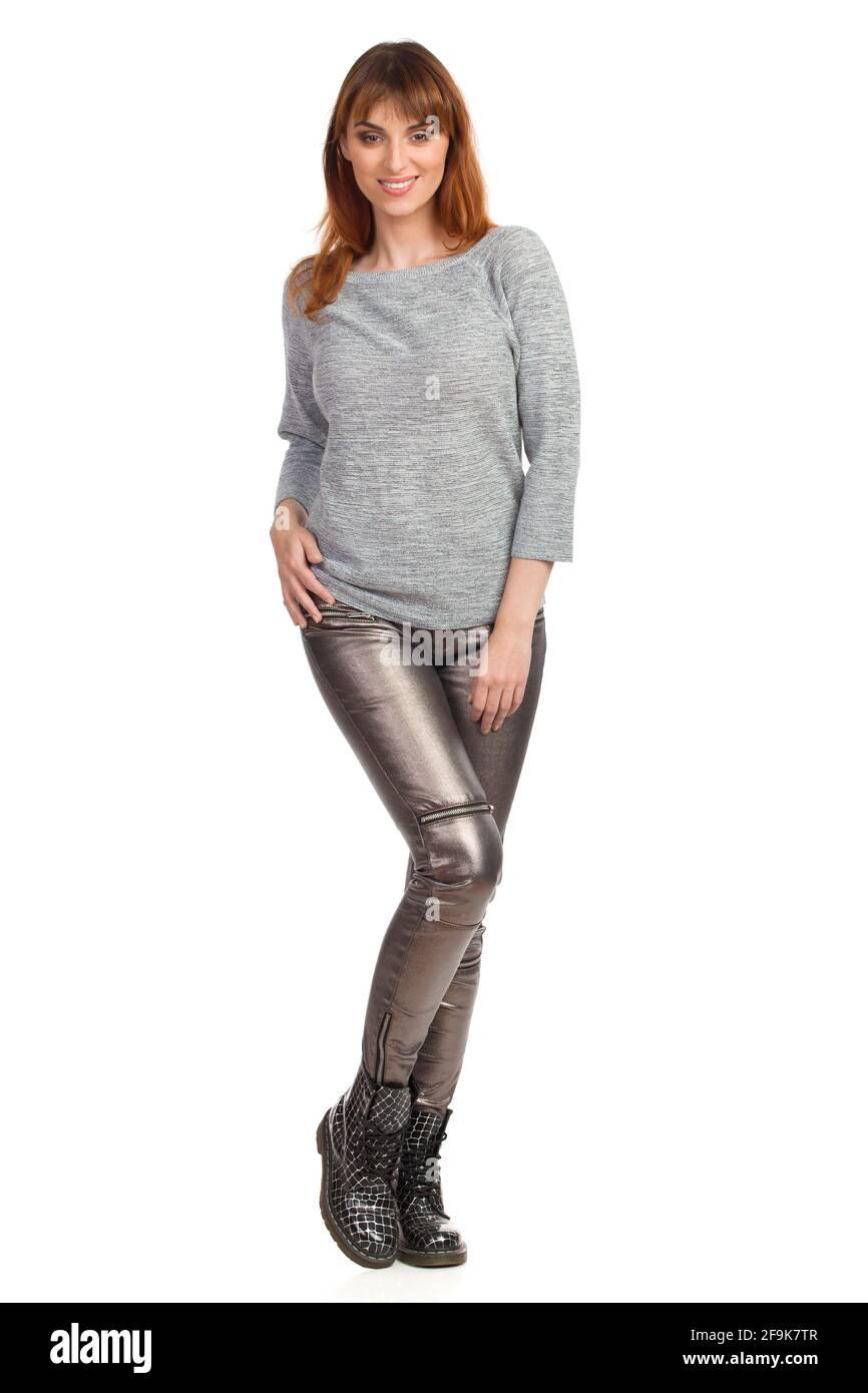 Mujer joven en blusa gris, pantalones brillantes y botas negras está de pie y sonriendo. Vista frontal. Estudio completo grabado aislado sobre blanco. Foto de stock