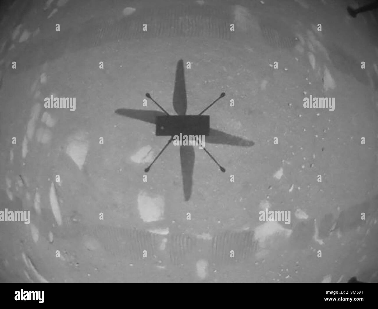 El helicóptero Ingenuity Mars de la NASA capturó este disparo mientras volaba sobre la superficie marciana el 19 de abril de 2021, durante la primera instancia de vuelo controlado y motorizado en otro planeta. Utilizó su cámara de navegación, que sigue el terreno de forma autónoma durante el vuelo. Foto del folleto por JPL-Caltech/NASA viaABACAPRESS.COM Crédito: Abaca Press/Alamy Live News Foto de stock