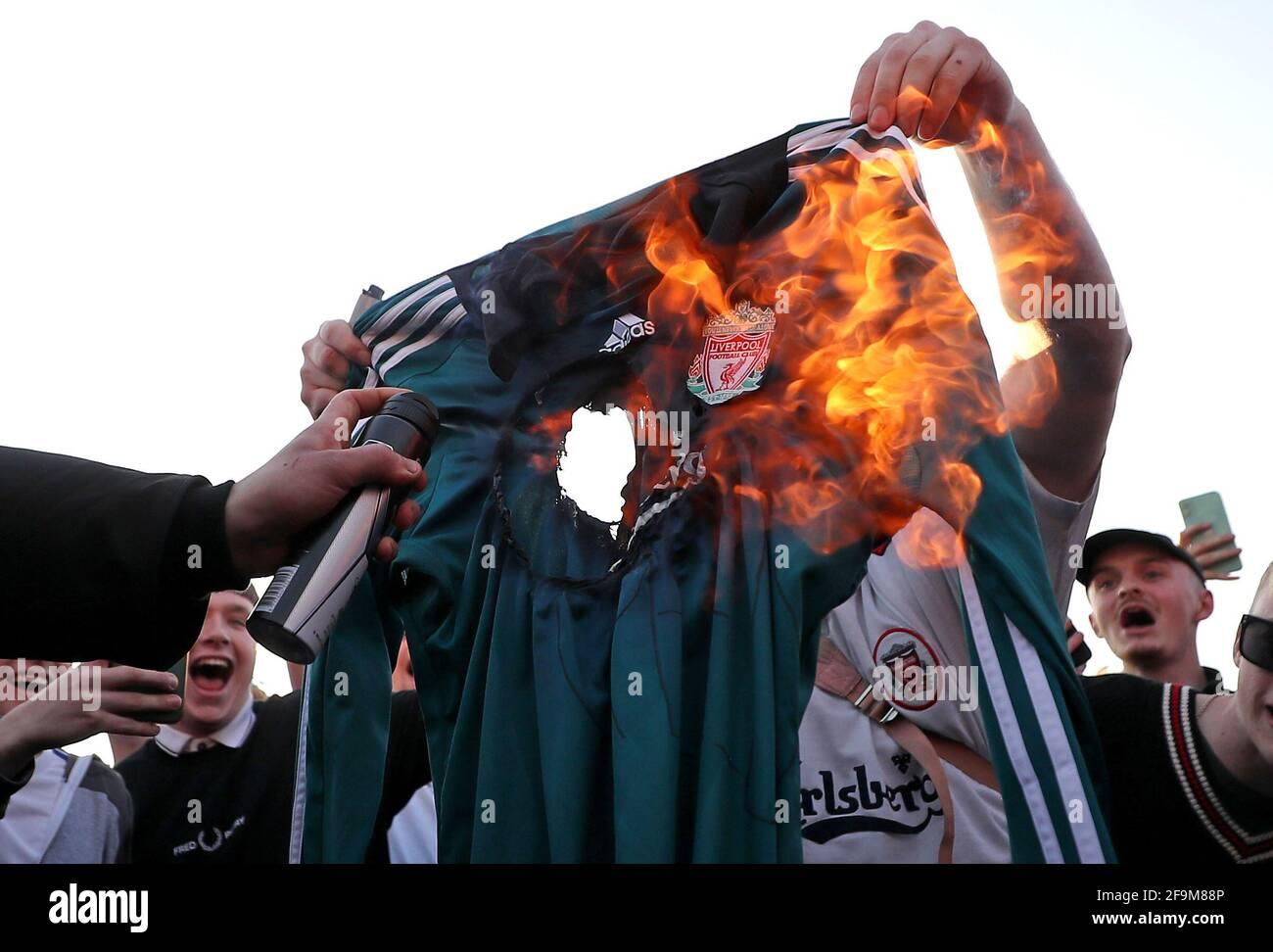 Los fans queman una réplica de la camiseta de Liverpool fuera de Elland Road contra la decisión de Liverpool de ser incluidos entre los clubes que intentan formar una nueva SuperLiga Europea. Fecha de la foto: Lunes 19 de abril de 2021. Foto de stock