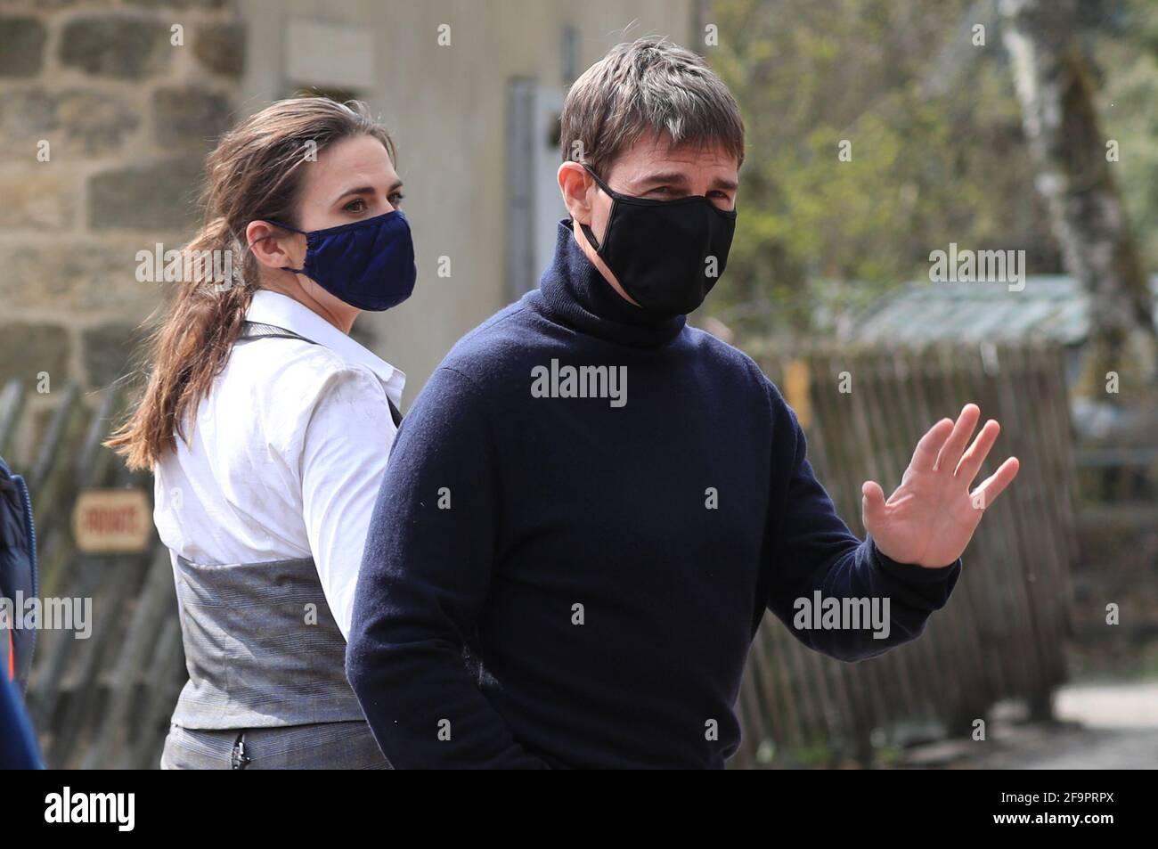 El actor Tom Cruise onlookers mientras camina hasta el conjunto de su último proyecto, que está filmando en los laterales de la estación de tren en el pueblo de Levisham en los moros de North York. Fecha de la foto: Martes 20 de abril de 2021. Foto de stock