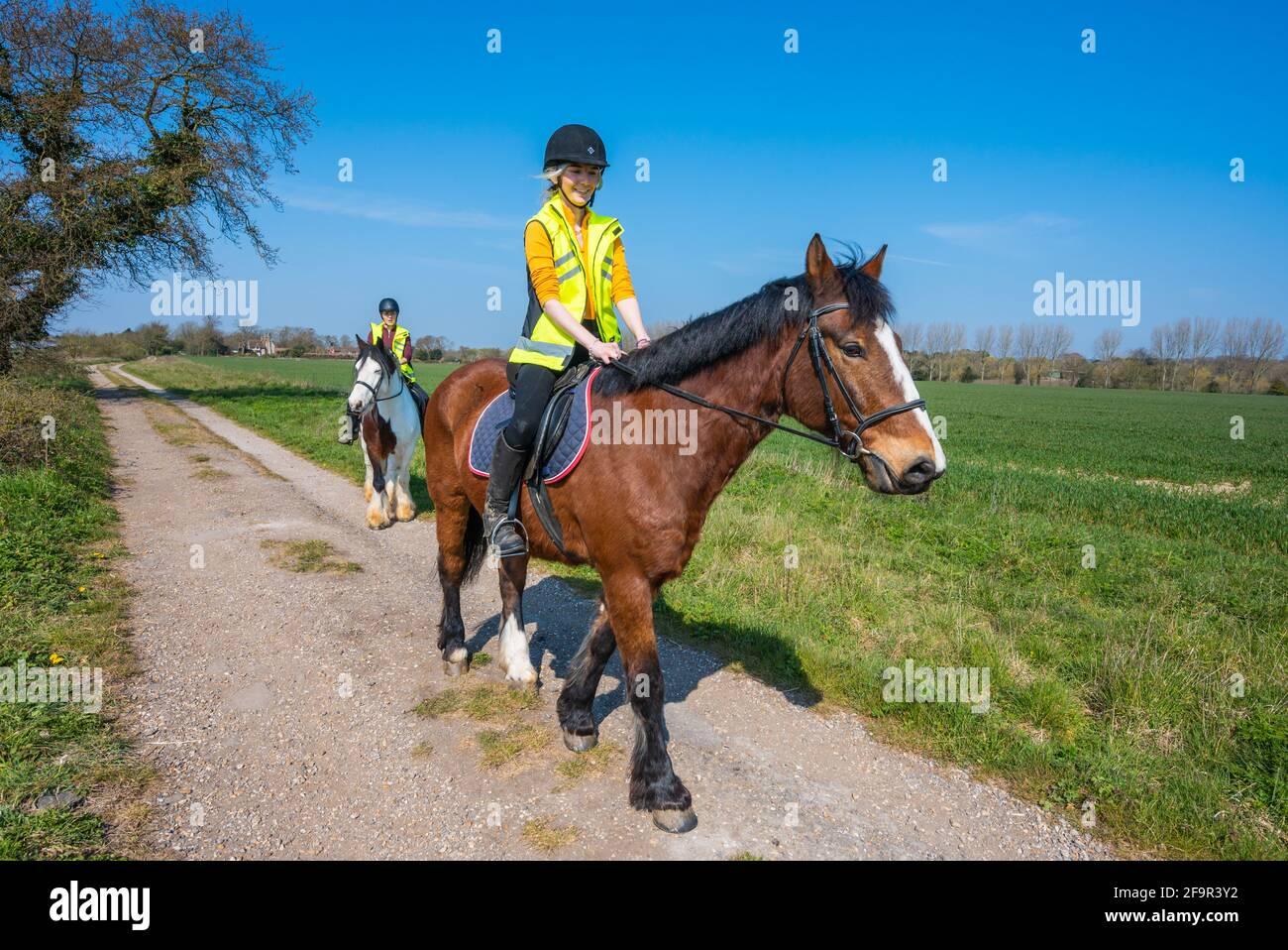 Mujeres jóvenes montando caballos en un camino rural a través del campo en un día soleado en primavera en West Sussex, Reino Unido. Paseo a caballo / jinetes. Foto de stock