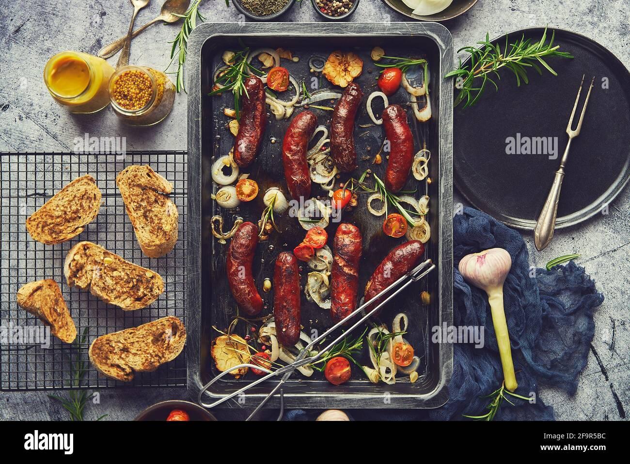 Deliciosas salchichas a la parrilla servidas en bandeja de metal oxidada con verduras a la barbacoa Foto de stock