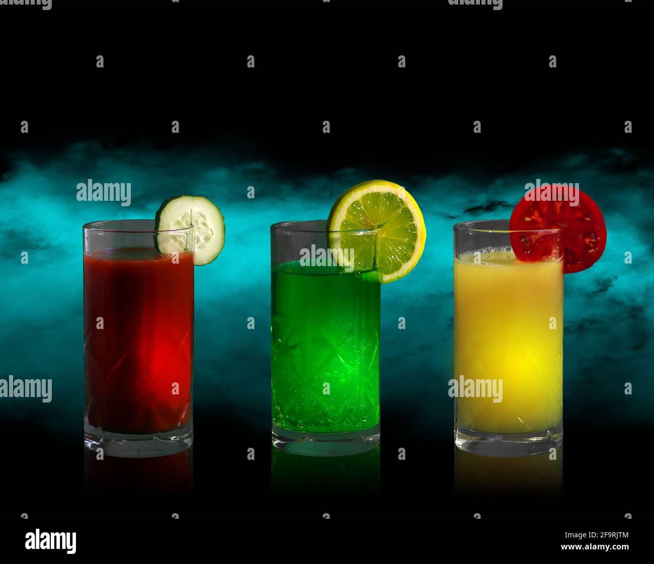 Tres vasos altos con bebidas de diferentes colores y rodajas de limón, tomate y pepino Foto de stock