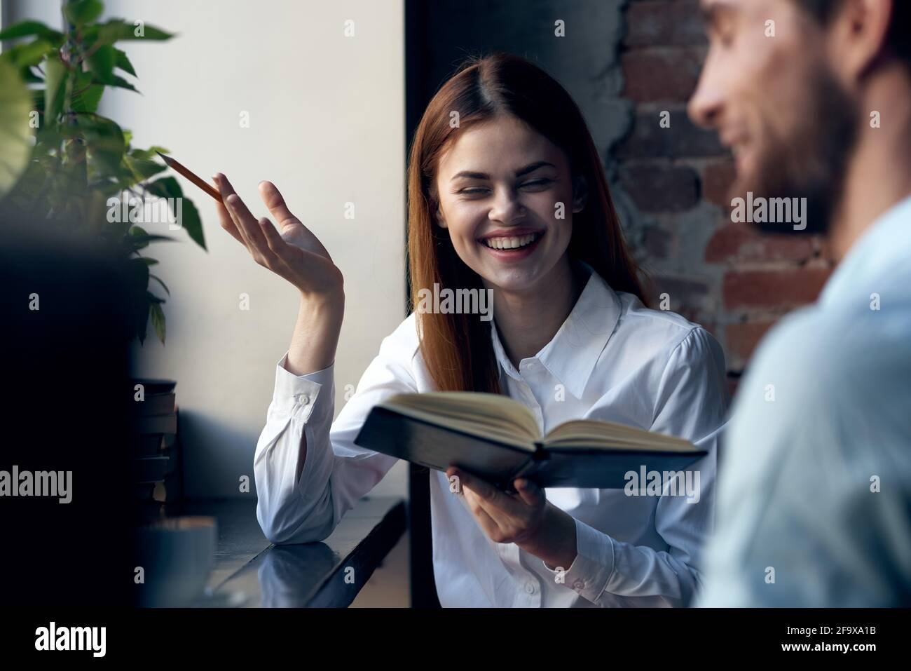 Mujer de negocios en camisa con libro en manos al lado trabajo de oficina Foto de stock