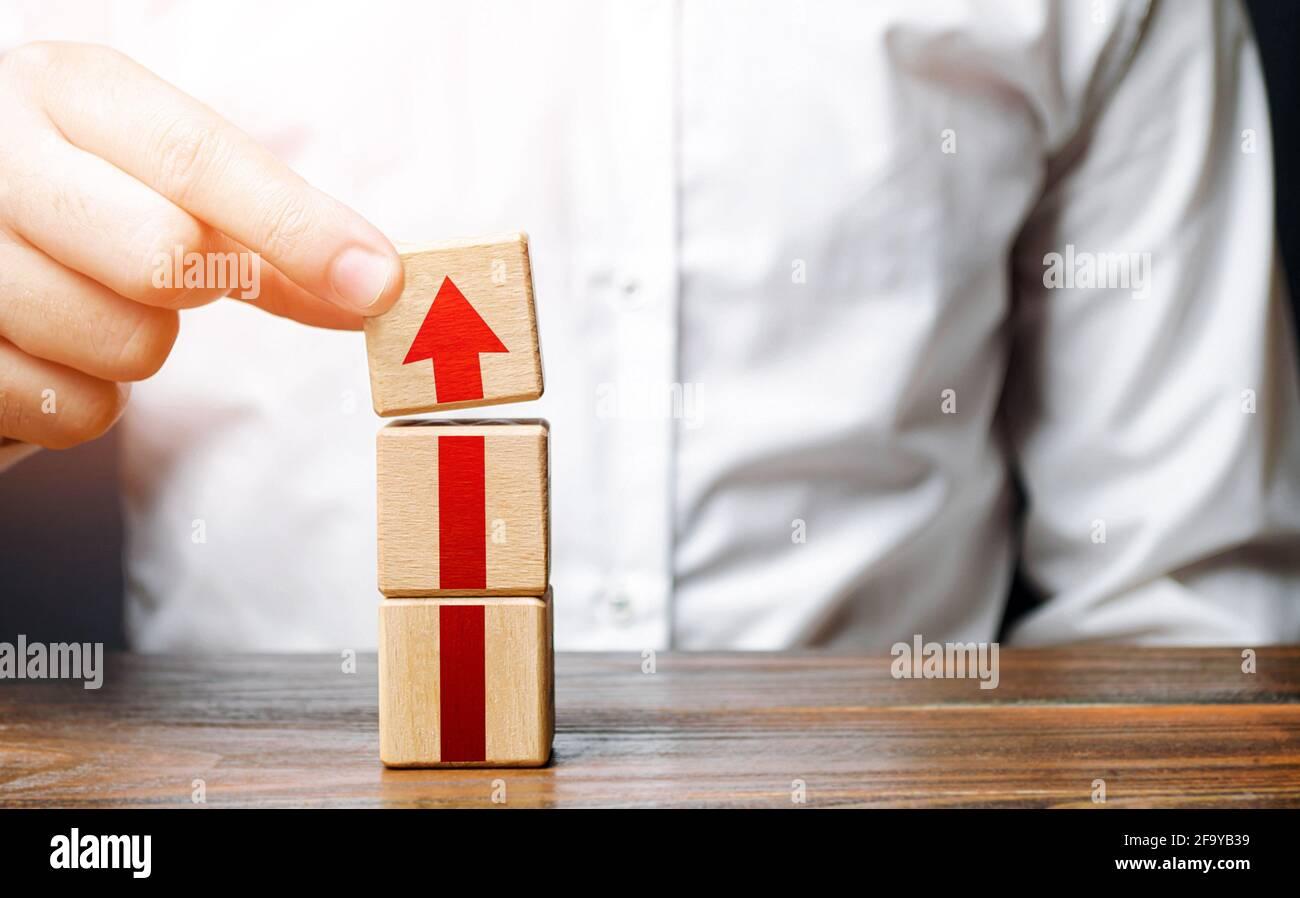 El hombre recoge una torre de bloques con una flecha. Crecimiento de la carrera paso a paso. Concepto de desarrollo a nuevos niveles. Expansión empresarial. Mejora de la calidad Foto de stock