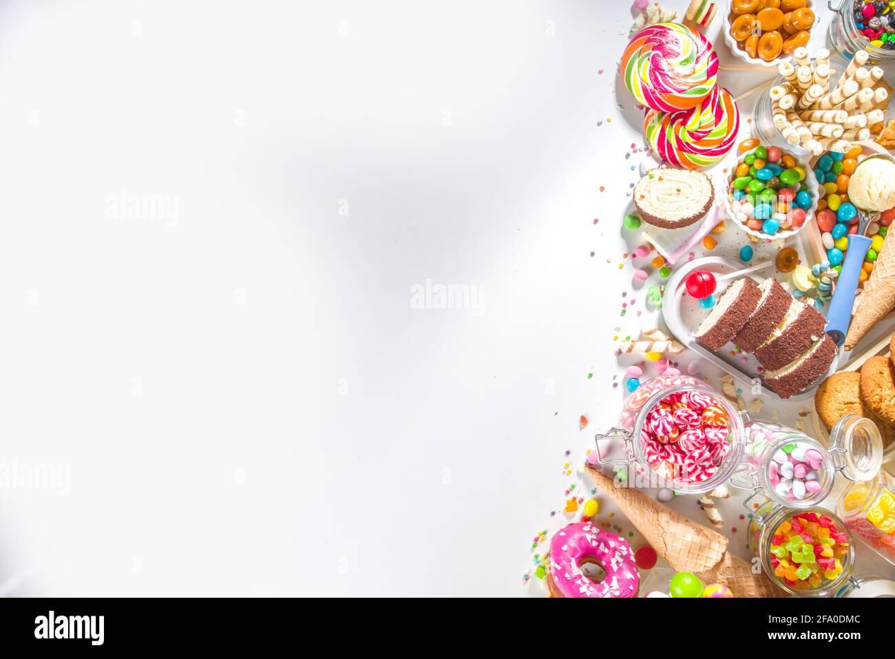 Selección de dulces coloridos. Juego de varios dulces, chocolates, donuts, galletas, piruletas, vista de la parte superior del helado sobre fondo blanco Foto de stock