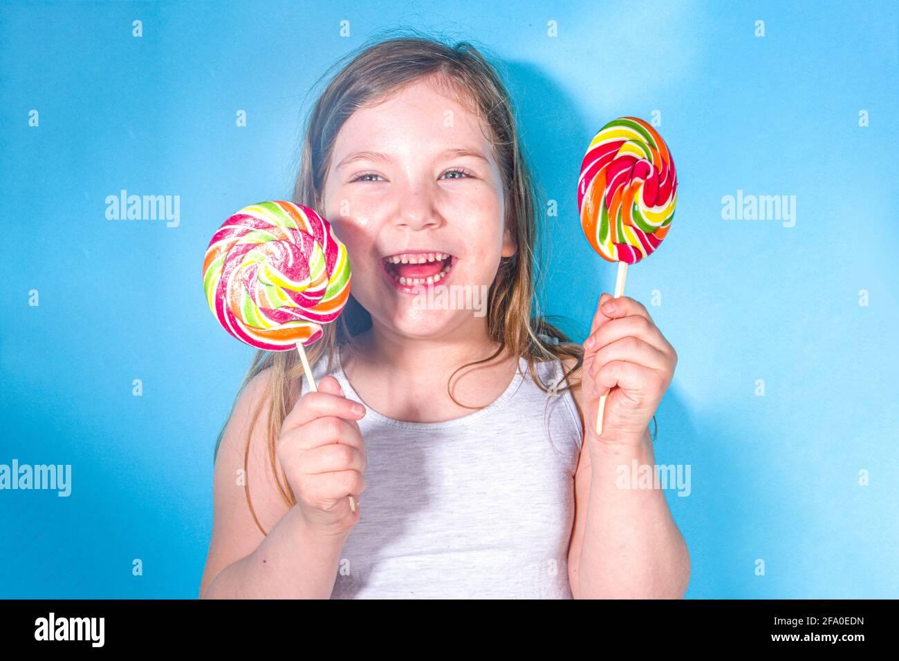 Pequeña chica divertida feliz con grandes y coloridos lollypops, vacaciones, felicidad, concepto de vacaciones de verano, Foto de stock